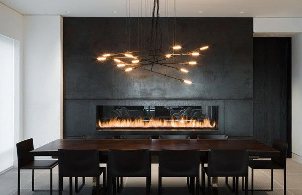 The Yorkville Penthouse, designed by Cecconi Simone, has a dining room with contrasting dark and light colors. Sitting adjacent to the massive, built-in fireplace wall that's covered in cold rolled steel, is a sleek, dark dining table and chairs with a custom chandelier.