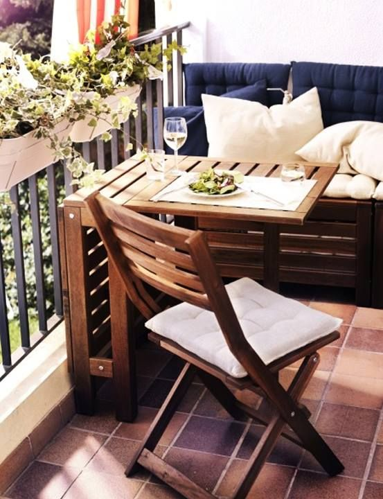 small 2-seat cushioned bench against the end of the balcony, small table for drinks/food/books, and a chair across.  I like this organization.    Bonus points for storage space under the bench!  And facing the bench, the other end of the balcony should be covered with plants and flowers!
