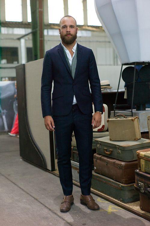 Porter un costume bleu marine, avec un brin d'originalité avec l'écharpe et les derbys double boucle.
