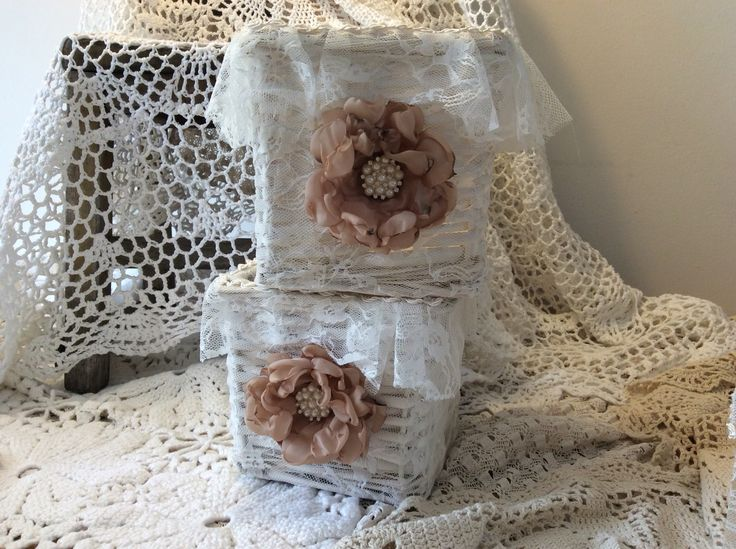 Shabby chic baskets covered with lace and decorated with flowers.