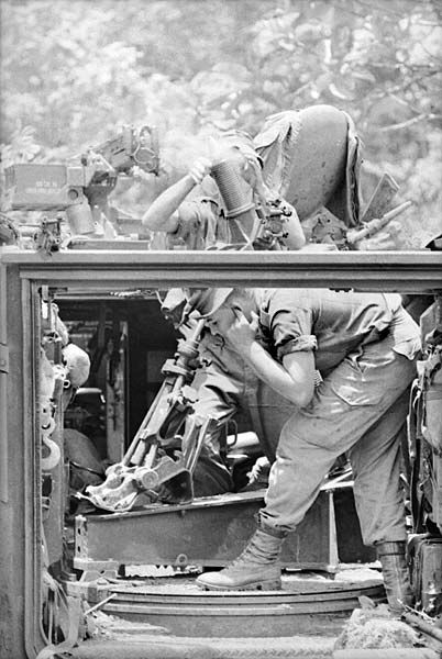 Troops of 6RAR fire an Armoured Personnel Carrier mounted mortar in the Long Tan area the day after the battle