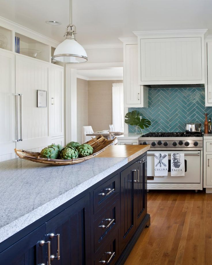 The dark tones of the island and the off-white cabinetry accentuate this kitchen's subtle coastal design. A teal backsplash adds a punch of color and cements the coastal feel.