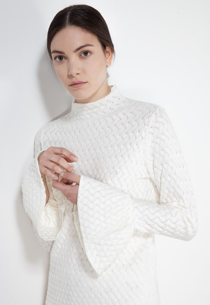 Stretch viscose sweater. Fabric characterized by a knitted stitch pattern with an embossed effect. Long corolla sleeves and wide neck. Skinny, tight-fitting design. Hip-length.