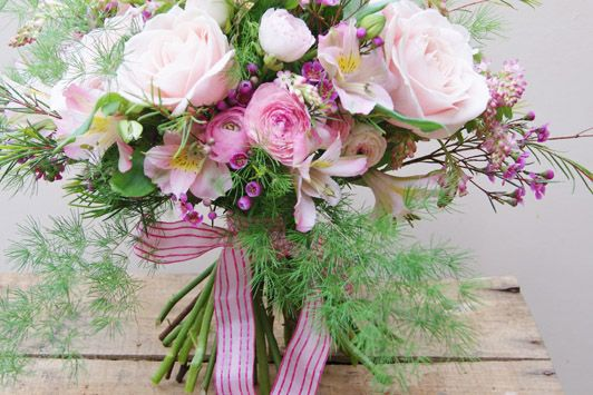 Spring garden hand-tied bridal bouquet of ranunculus, sweet avalanche roses, waxflower and alstroemeria. With it's trailing wispy asparagus fern and blossom and pretty ribbon, this would be lovely for a rustic, informal wedding. Florissimo, Shropshire