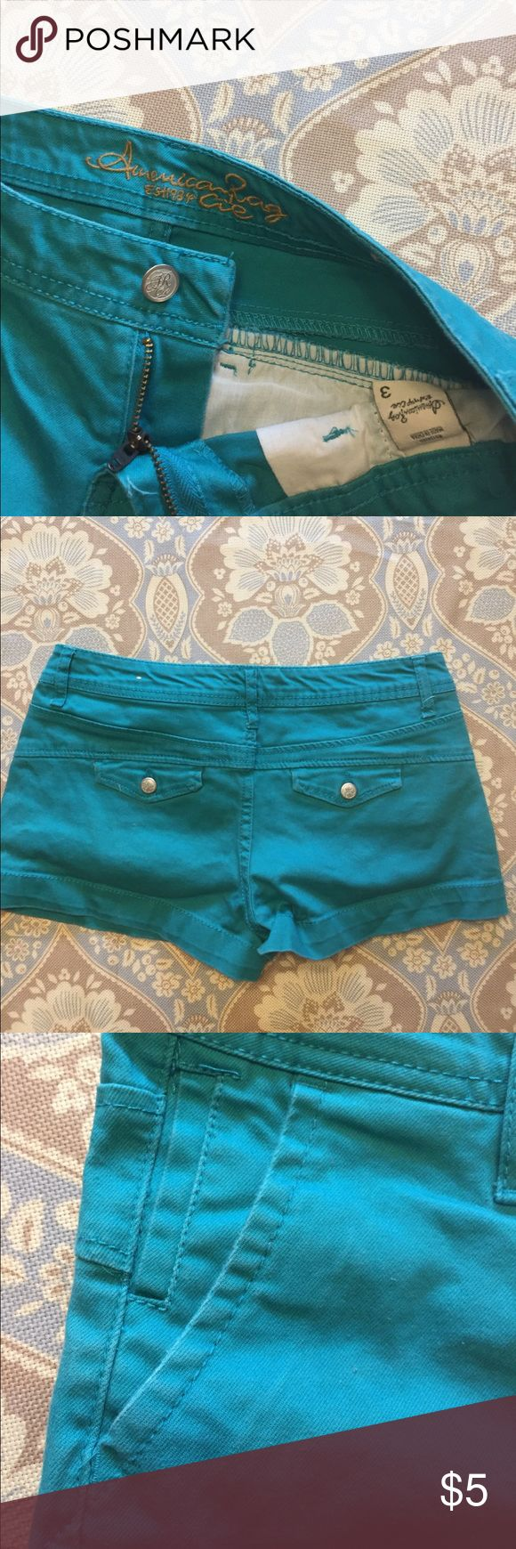 Women's turquoise shorts Size 3 gently used shorts. Color vibrant except some slight fading near the pockets (pictured).  Slightly loose thread (pictured) near the crease. Very comfortable and in great condition. Material is stretchy and mid/low rise. American Rag Shorts