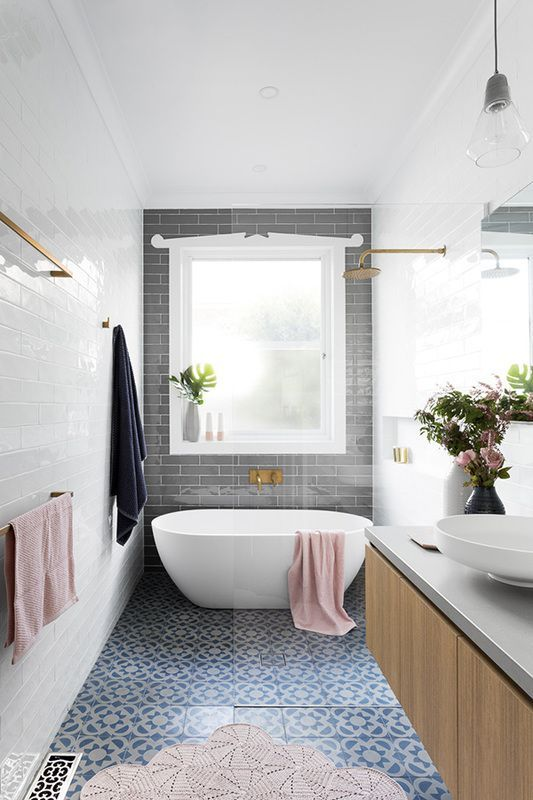 Bright bathroom with beautiful blueish tiles and a freestanding tub. Great soft pink color accents and a golden shower head. If you want to know how to deal with challenging conditions, check out our blogpost!