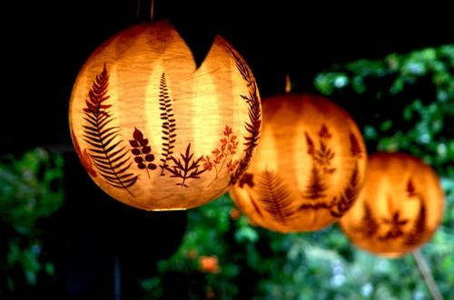 Botanical lanterns - glue ferns, leaves on paper lanterns, decoupage layers of orange tissue paper on top of leaves using modpodge or mixture of 1/2 white glue + 1/2 water...