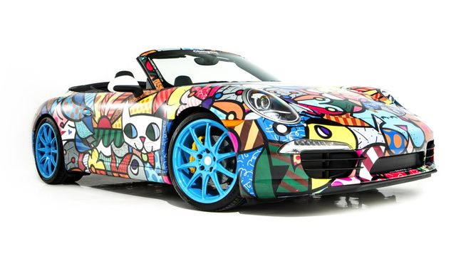 Wow!!  Look at those wheels.  Neo-pop artist Romero Britto art on A Porsche 911 Cabriolet.  How cool is that!!