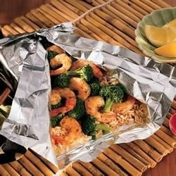 Shrimp, broccoli, and rice cook together with garlic and seasonings in foil packets for a flavorful, fuss-free dinner.