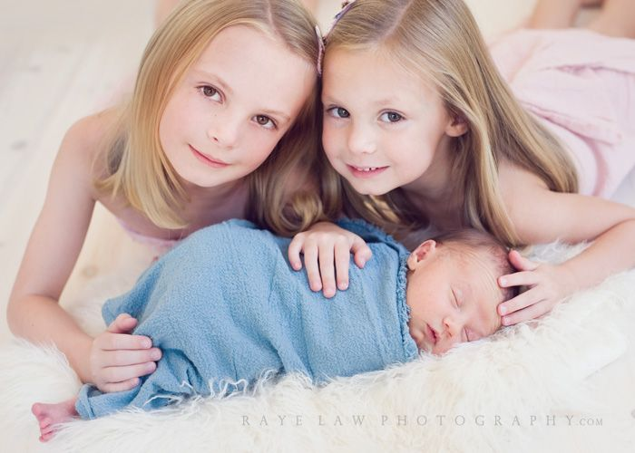 2 older Siblings with new baby pose
