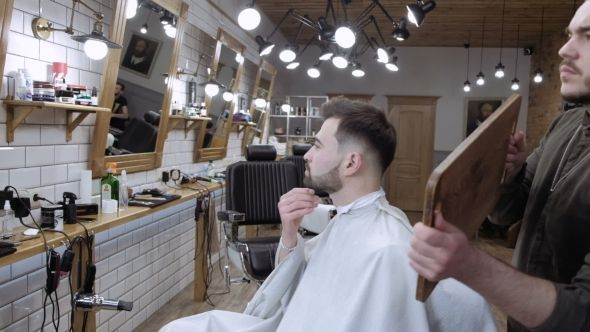 The Barber Holds Up a Mirror and Shows Real Client Back in the Barbershop