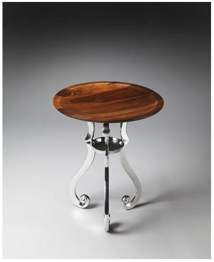 El tablero de la mesa en forma de bandeja en madera de mango sólido acabado en unos tonos marrones ondulantes encima de una base de metal doblado y curvado resplandeciente.