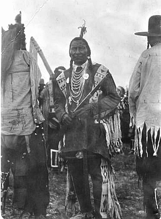 1910 Wolf Plume wearing necklaces over traditional beaded regalia holds firearm while standing next to other Indians .