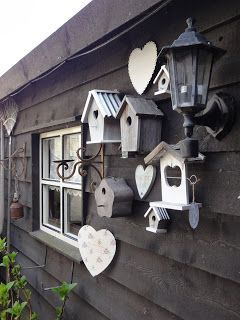Beautifully painted birdhouses displayed as a collection, love this look....