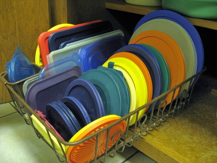 Use a dish drainer to organize pot lids, or Tupperware lids in a cabinet.  You can find them in all sizes now, to fit almost any cabinet, and they are super cheap at the dollar store