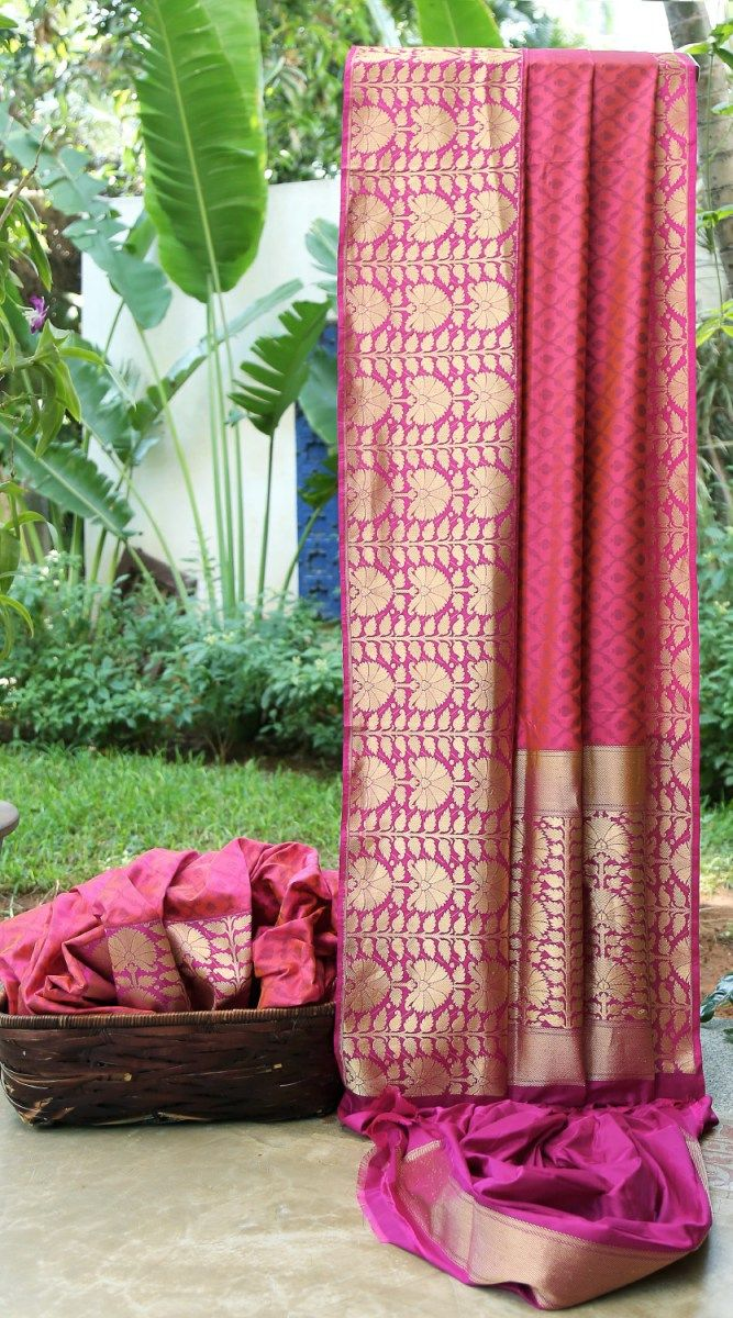 This Benares silk is in pink with a thread work pattern in mauve all over the sari. The border is in purple on one side and magenta on the other side, with a bold gold zari pattern. The pallu is in…