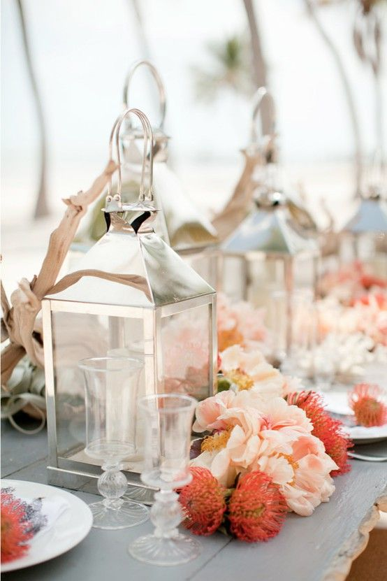 silver lantern centerpieces and tropical looking flowers in peach and coral...would put candles inside the lantern instead for table centerpieces at a night wedding reception
