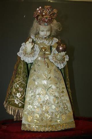 Enfant Jésus, en cire, bénissant et tenant le monde, vêtu d'une riche robe enrichie de broderies, repose sur un socle ovale en bois noirci, manque le globe. Fin du XIXème siècle. H. 46 cm.