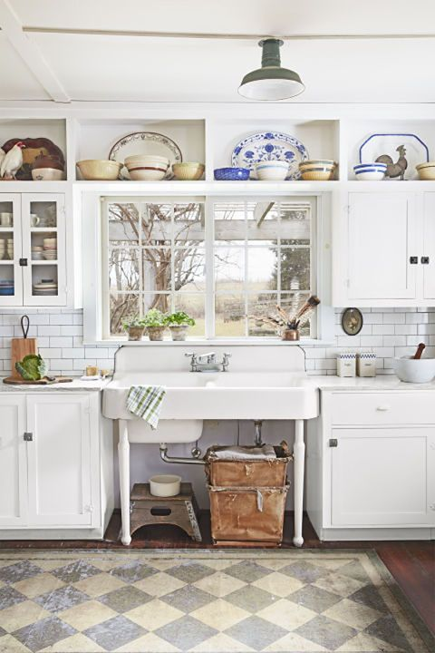 Vintage Sink:  This couple embraced the history of their 18th-century farmhouse by filling it with antiques, and in the kitchen, that translates to a vintage porcelain double farm sink and a display of gorgeous antique dishes. Other small touches, like the faded checkered rug and storage baskets under the sink, add to the rustic style.