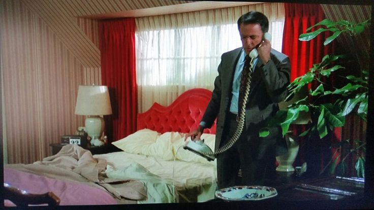 Hollywood Regency bedroom with red draperies and tufted velvet headboard seat against a window.  From the 1976 movie, Freaky Friday.