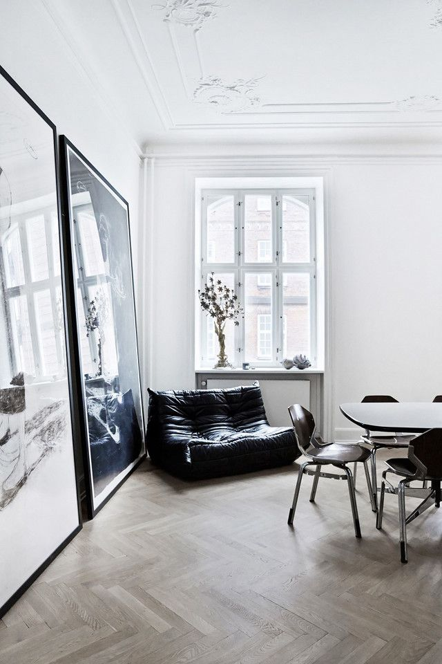 Dining room with herringbone floors, large art propped against the wall, and a black leather bean bag