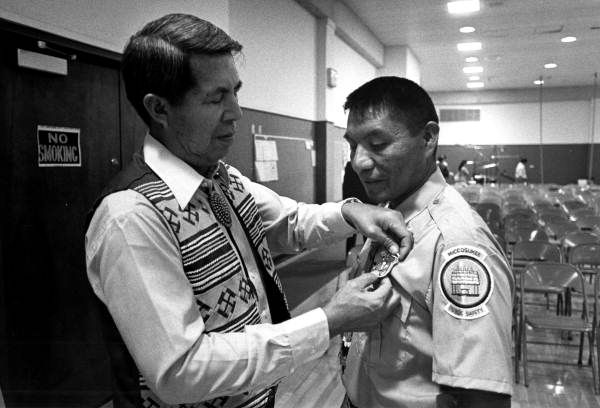 Buffalo Tiger pinning badge on Don Osceola during criminal justice graduation at the Miami-Dade Community College, 1977