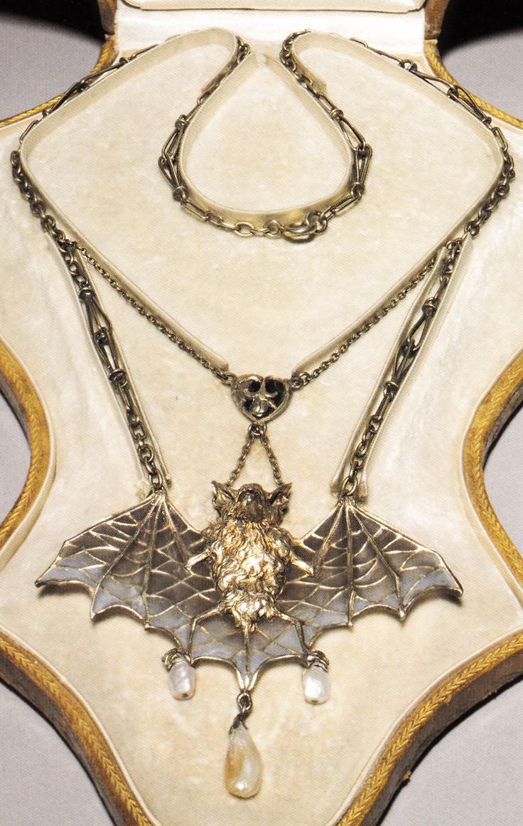 An Art Nouveau 'Bat' necklace, attributed to Lucien Janvier, circa 1900. Composed of silver, silver gilt, plique-à-jour enamel and pearls. Symbols of the night, bats were a common grotesque motif in Art Nouveau jewellery, as seen in this piece. Source: Artistic Luxury - Fabergé Tiffany Lalique #Janvier #ArtNouveau #necklace
