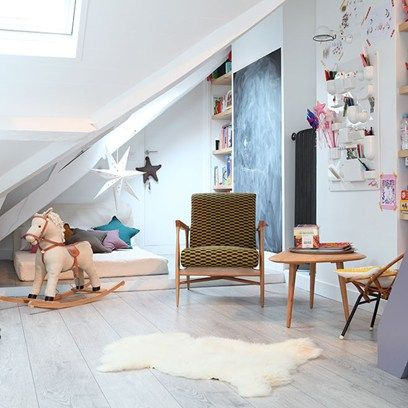 This Parisian loft playroom makes good use of restricted space with playful hanging components on the wall, a blackboard which is both useful and decorative and a snug day bed tucked under the eaves. The clean, white wooden floors give the room a more spatious feel in keeping with the clean lines of the scandinavian style armchair.