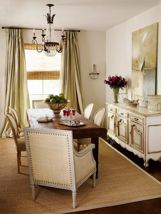 Lovely neutral color scheme, fantastic billowy drapes.  The woven shade and sisal rug bring needed texture, as do the linen fabric and nailhead trim on the end chairs.  I'd love to see a richer color on the walls.  bhg.com