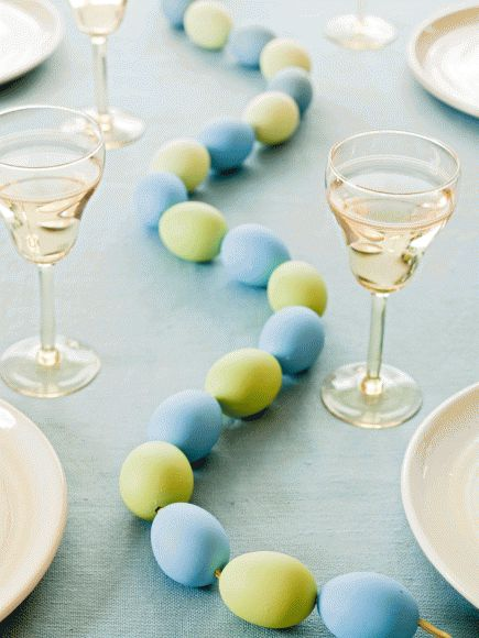 Plastic or blown-and-dyed eggs make a pretty weave down the middle of your table. More spring decorating ideas: http://www.midwestliving.com/homes/entertaining/spring-centerpieces/page/29/0#