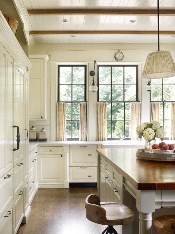 Appliances such as the dishwasher and refrigerator/freezer are covered in cabinetry rather than metal. Lantern-styled sconces by the windows evoke a New England flair.