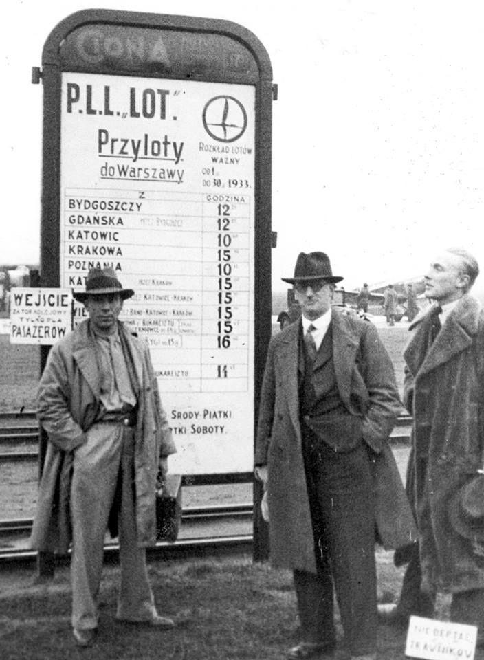 """Warszawa - pasażerowie przed tablicą rozkładu lotów na lotnisku. Widoczne logo (żuraw) i napis P.L.L. """"LOT"""" (kwieceień 1933 r.)."""