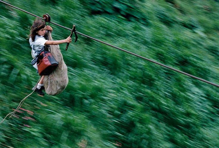 Andare a scuola in Colombia.I ragazzi devono scivolare I ragazzi devono scivolare attraverso 400 metri di filo metallico da una sponda all'altra del fiume per raggiungere la scuola.