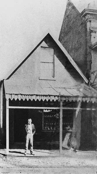James Davis poses in front of his crockery store, George Street, Brisbane, ca. 1872