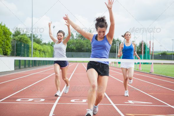 Female athlete celebrates win at finish line at track field ...  20s, active, activity, athlete, athletic, athletics, caucasian, celebrating, challenge, cheering, competition, competitive, exercise, female, field, finish line, fit, fitness, health, healthy, heat, jogging, leisure, lifestyle, looking away, outdoors, physical, race, racing, run, runner, running, shouting, sport, sports, sporty, stadium, tied hair, track, training, winner, winning, woman, young adult
