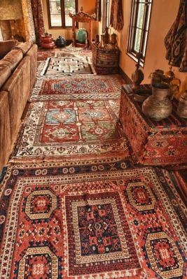 A melange of Turkish and native American carpets lends warmth and color to the living room. The far end of the room features a Tibetan gong and stand and various pieces of Burmese lacquer. Caucasian soumak besiks cover the tables on the right side of the room, bearing a collection of middle eastern teapots and jugs.