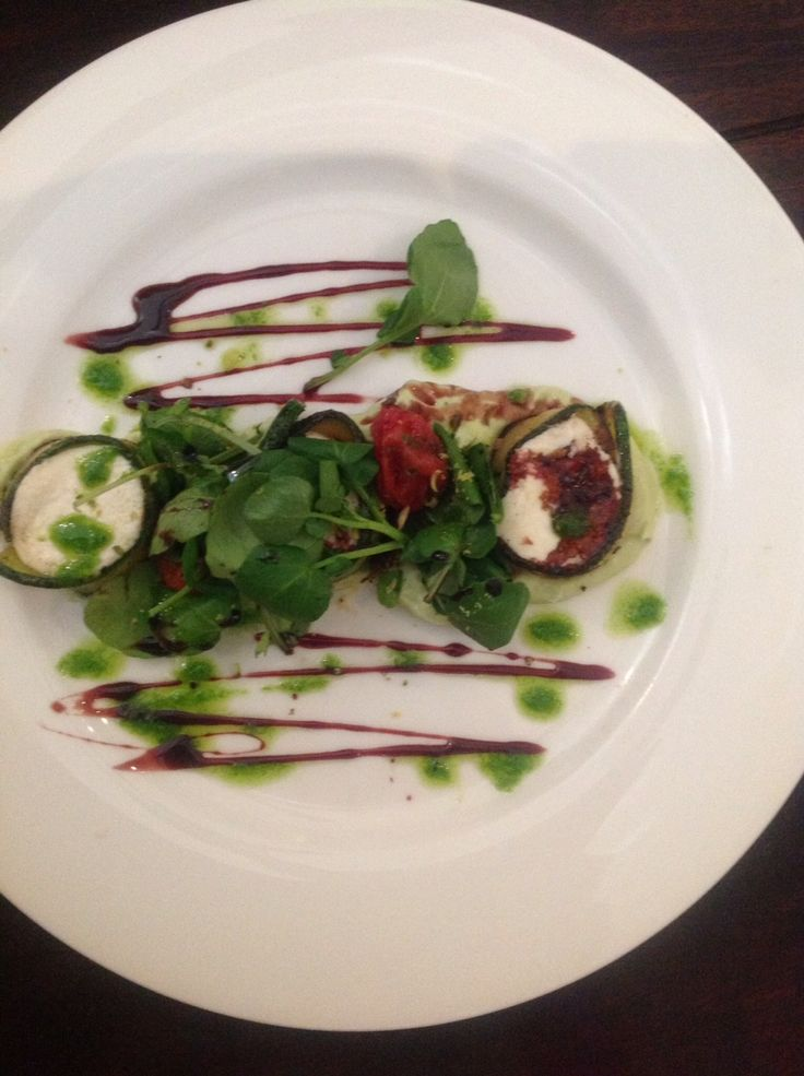 Grilled Goats Cheese wrapped in Zucchini Ribbons accompanied by Avocado Mousse, Watercress, grated Pistachio Nuts  and a Port Wine Dressing
