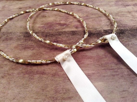 Modern and very elegant stefana. Matching with all style of weddings.  Handmade with twisted brass gold metal base. The base from the one side has stripes. All around the base there are ivory pearls.  At the back side there is an ivory satin ribbon which makes a simple tide and connects the stefana together. On the ribbon there is a pearl. You receive the stefana in a box with two matching boutounnieres  See also the silver edition here…