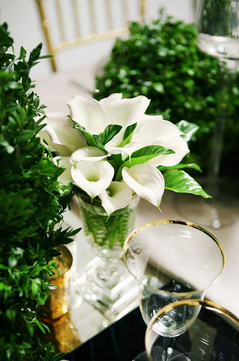 A dozen white calla lilies packed in a glass vessel make a chic statement.