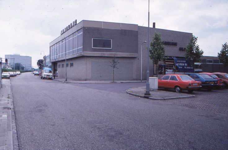Almelo, Parallelweg ter hoogte van de achterkant van het station Almelo, met aan de rechterzijde de afslag naar de Dijkstraat. Op de achtergrond het fabriekscomplex van de WUBA (Warmink Uurwerken & Barometers Almelo) en op de voorgrond het bedrijf van Almeline. Beide bedrijven stonden later op de nominatie om te worden afgebroken, ten behoeve van nieuwbouw voor het ROC Twente.