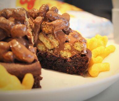 Den här kladdkakan med ostbågar kan få vem som helst att börja dregla. För visst får kombinationen sött och salt det att vattnas i munnen! En klassisk kladdkaka toppas med världens enklaste topping – ostbågar varvade med smält mjölkchoklad. Bjuds med fördel på cheez doodle day den 5 mars.