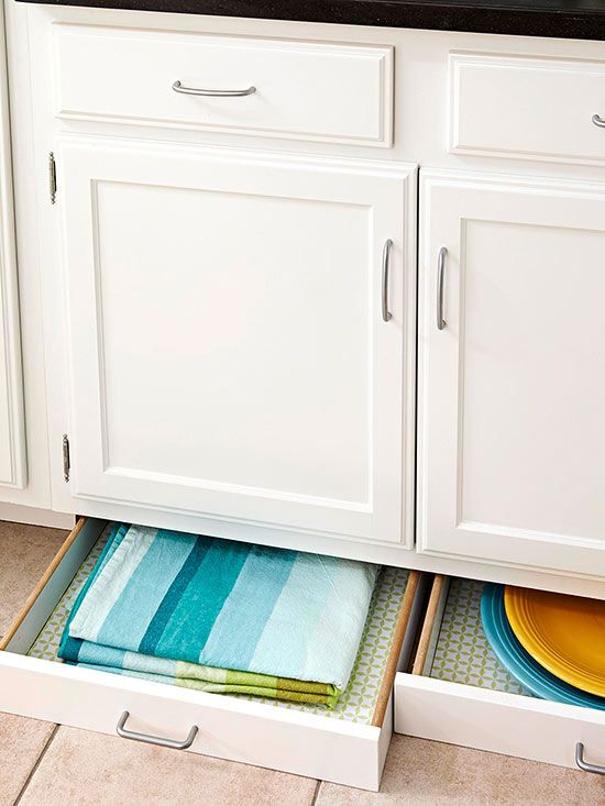 In a small kitchen, every inch counts. Instead of a solid toe-kick, extra storage space is built in beneath the cabinets. These broad, shallow drawers at the base of the storage wall are perfect for small items like linens and platters.