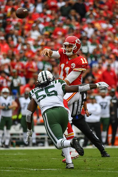 Quarterback Alex Smith of the Kansas City Chiefs throws the ball just ahead of the sack threat from outside linebacker Lorenzo Mauldin of the New...