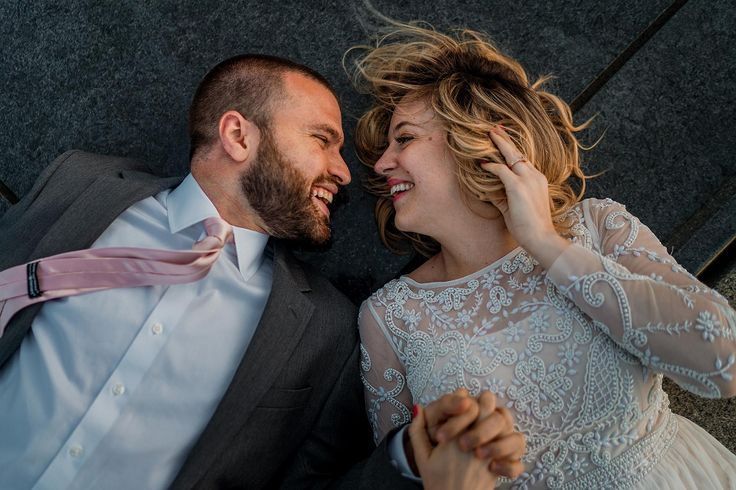 Bride and groom laying on the ground in front of the us
