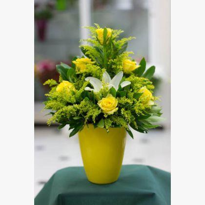Σύνθεση λουλουδιών σε κίτρινες αποχρώσεις, με κίτρινα τριαντάφυλλα και λευκό λιλιουμ.