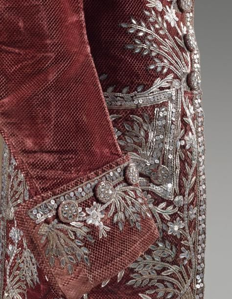 Detail, cour coat and breeches, second half 18th century (Louis XVI). Garnet red cut silk velvet lavishely embroidered in a design of flowers and foliage trimmings made of silver and gold sequins and faceted glass.
