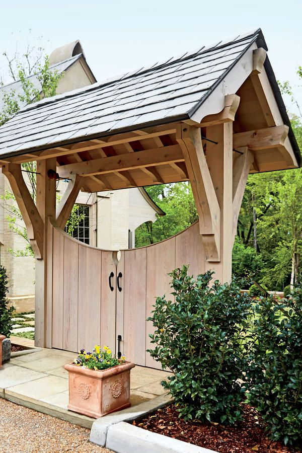 Friendly Folly - Best New Home - Southernliving. A charming entry gate, constructed with cedar timbers and a slate roof, creates a memorable walk from the guest parking court to the lush courtyard beyond.