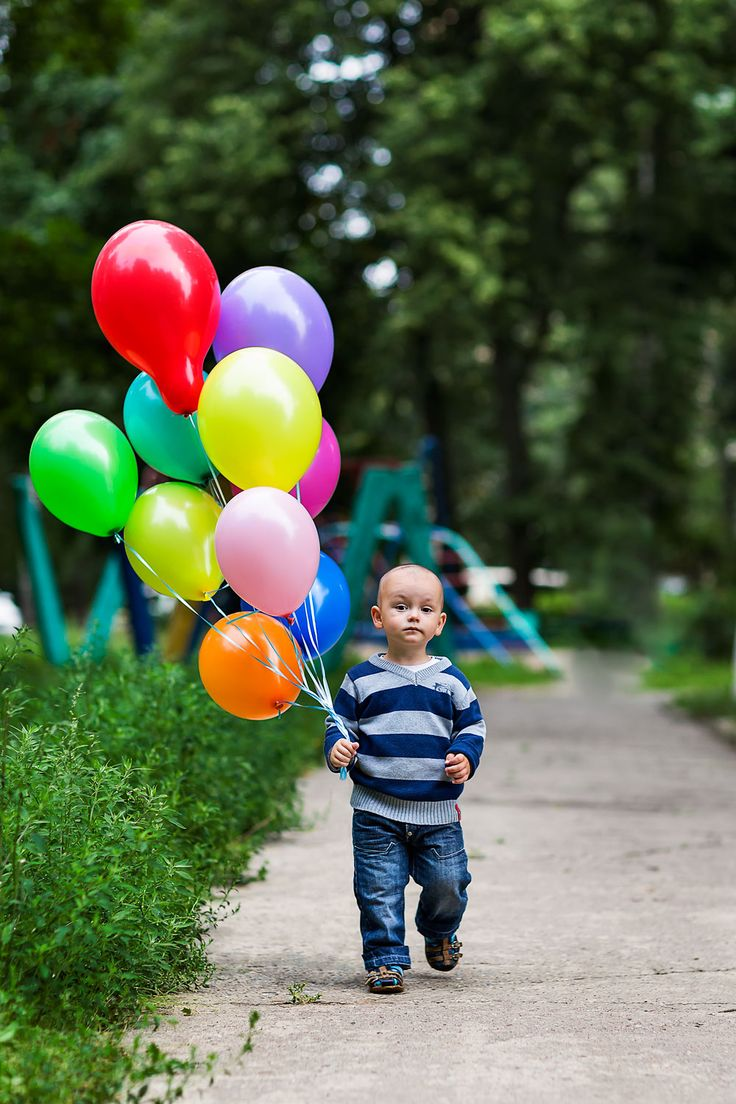 boy with colorful balloons filled with helium