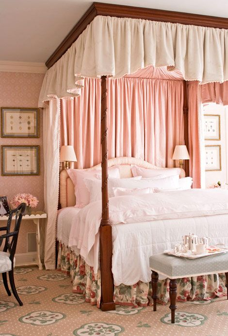 A master bedroom in pretty pinks features a feminine canopy bed and floral details - Traditional Home® / Photo: John Bessler / Design: Janet Simon