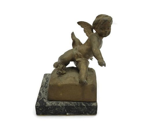 A lovely antique Victorian bookend featuring a winged cherub on a marble base.  Measures about 6 tall. Marked with a foundry coin mark Brig Paris